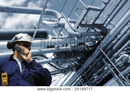 engineer in hard-hat with large refinery pipelines in background, blue toning background