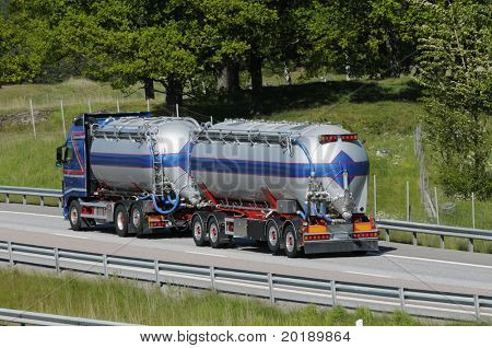 large fuel truck, fuel tanker driving on freeway.