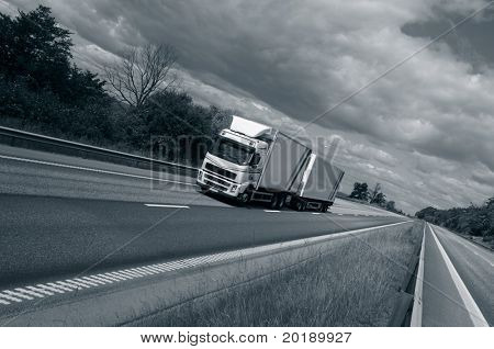 truck driving on highway, slightly tilted perspective and in a bluish toning concept