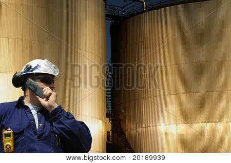 engineer in front of two sunlit fuel-storage tanks, concept industrial shot.