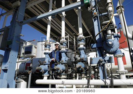engineer behind pipelines at large fuel depot inside oil and gas refinery