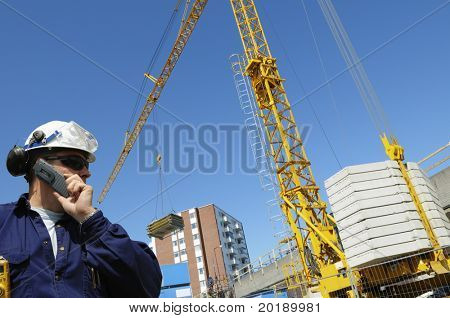 construction engineer in front of mobile crane inside building-site