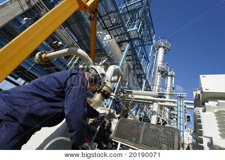engineer working inside large oil and gas refinery, chemical plant.