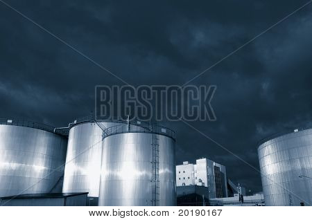 fuel storage tanks under a stormy sky, dark bluish duplex toning idea