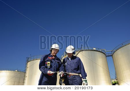 engineers and sunlit oil storage tanks, shot from a low-angle