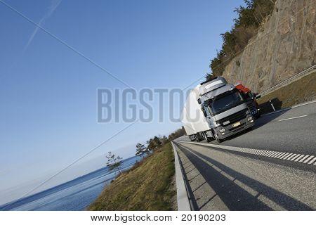 Große LKW fahren auf der Autobahn mit der malerischen Umgebung von Meer und Berg-pass