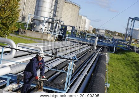 engineer turning on pipeline pump leading to refinery tanks