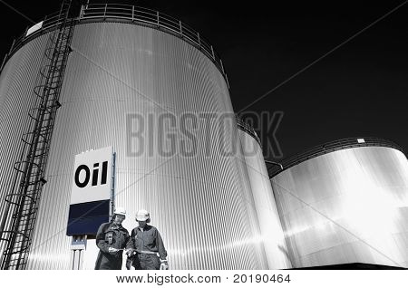 oil engineers and industrial fuel-storage tanks, large commercial oil-sign, sot taken inside oil-refinery. dark silver duplex toning concept