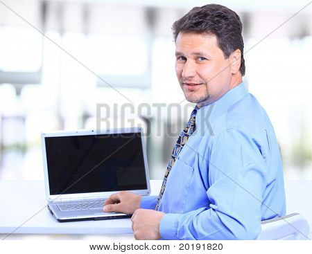 Portrait of a happy man entrepreneur displaying computer laptop in office