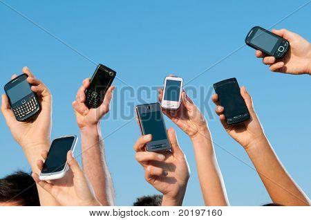 Gente feliz mostrando sus teléfonos móviles modernos contra el cielo azul