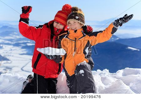 Two happy children waving in snow on a sunny mountaintop.