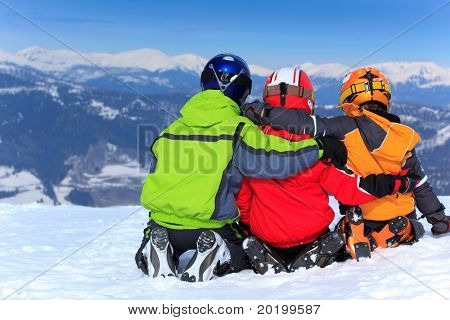 Three young children in ski clothes and helmets on snowy Alpine summit.