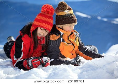 Two children the snow ski wearing winter coats and knit hats in winter.