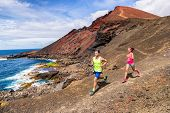 Trail running couple runners racing on mountain path in volcanic rocks nature landscape in summer ou poster