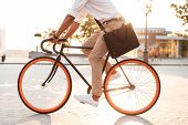 Cropped picture of handsome young african man early morning with bicycle walking outdoors. poster