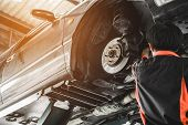 Car Lifted In Automobile Service For Fixing. Mechanic Male In Garage Automobile Checking poster