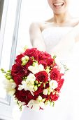 stock photo of floral bouquet  - smiling bride tossing bouquet - JPG