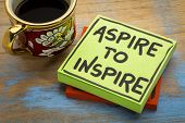 aspire to inspire reminder  or advice - handwriting in black ink on a sticky note with a cup of coff poster