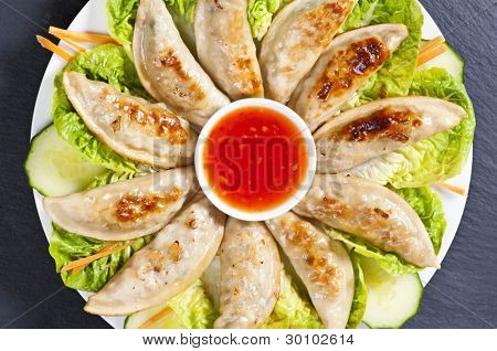 Fried Jiaozi with chilli sauce and salad