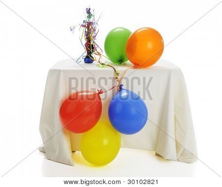 Five helium balloons with tangled ribbons attached to a festive weight.  The balloons are drooping over the table now that the helium has gone.  On a white background.