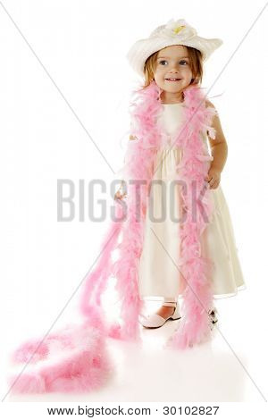 A beautiful preschooler dressed totally in white with a feathery pink boa draped over her shoulders.  On a white background.