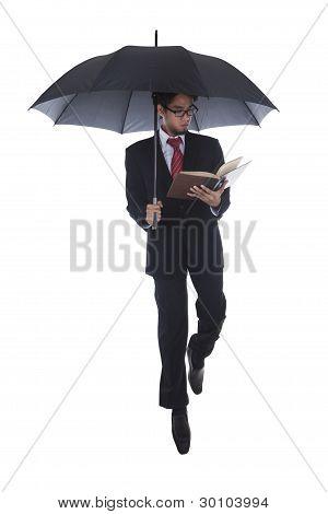 Businessman Reading A Book Under Umbrella