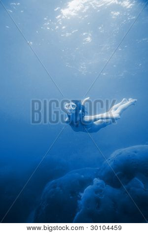 Young woman freediving in a clear blue sea near coral reef