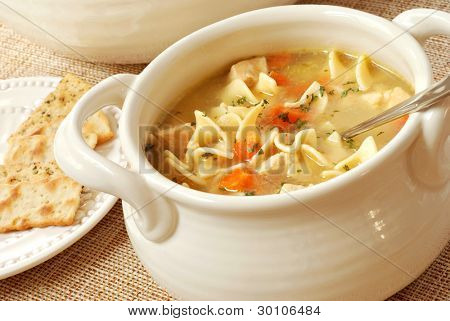 Chicken noodle soup in cream colored ceramic bowl with handles.  Plate of crackers and soup tureen in background.  Closeup with shallow dof.
