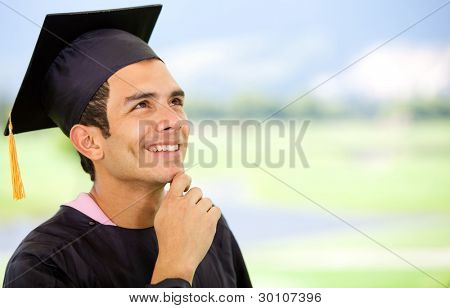 Thoughtful graduation man wearing a mortarboard and looking up