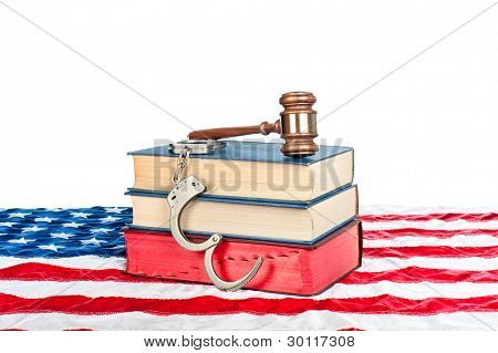 Gavel, law books and handcuffs resting on an American flag with a white background for placement of copy.