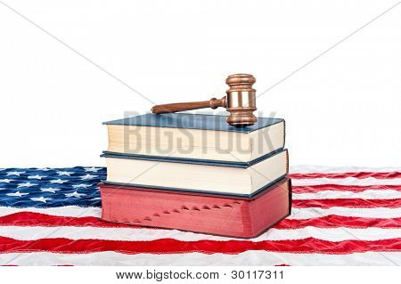 Gavel and law books resting on an American flag with a white background for placement of copy.