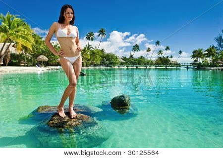Young woman in white bikini standing next to tropical beach