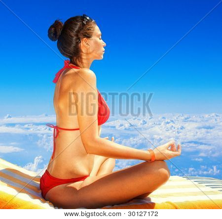 young woman sitting in lotus position on a background of blue sky