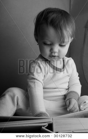 Black And White Portrait Of A Toddler Reading A Book In A Tent