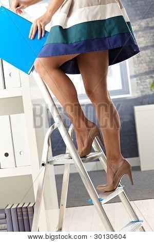 Pretty office assistant in short skirt standing on ladder, organizing file folder.?