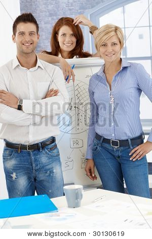 Portrait of happy businessteam standing at whiteboard in meeting room, smiling at camera.?