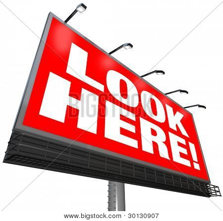The words Look Here on a red background on a large outdoor billboard to attract attention and advertise a message or business or get people to notice a message