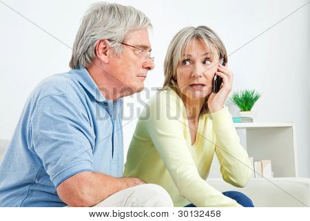 Senior woman talking on cell phone at home in living room