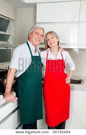 zwei glückliche ältere Leute mit Schürzen in der Küche