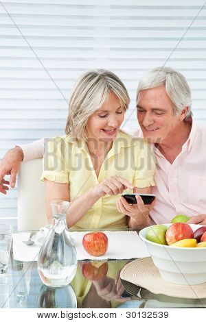 Senior couple using smartphone at breakfast table