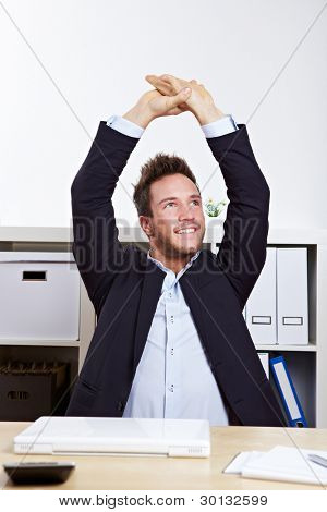 Happy business man in office stretching his back at desk