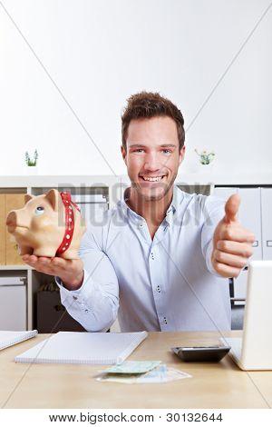 Hombre de negocios feliz con hucha sosteniendo los pulgares en la oficina