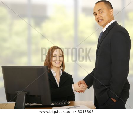 Business People Smile At Camera While Shaking Hand