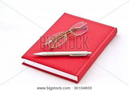 Glasses and the pen on the book