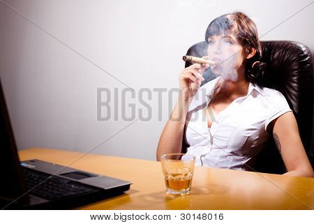 Young Businesswoman Chillingg In Her Office, Smoking A Cigar And Drinking Whiskey