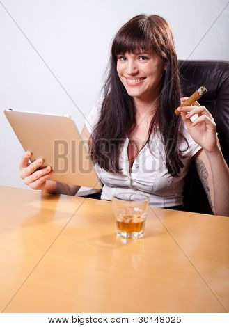 Young Businesswoman Relaxing In Her Office, Using Tablet Computer, Smoking A Cigar And Drinking