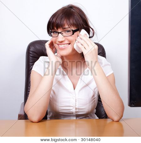 Cheerful Young Businesswoman Chatting On The Phone In Her Office