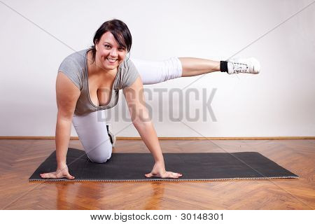 Playful Overweight Woman Exercising On The Floor