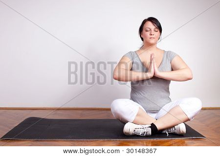 Overweight woman in a yoga position at home