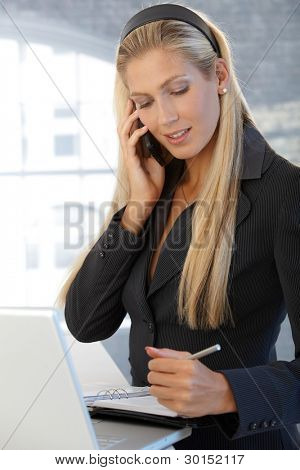 Smiling confident businesswoman writing notes into personal organizer, speaking on mobile phone, standing in office.?